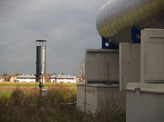 Pohled od fermentační stanice směrem k obytné zástavbě, která je vzdálená cca 200m. Napravo je vidět část rourového fermentoru, nalevo bezpečnostní fléra, kde je spalován bioplyn v případě odstávky kogeneračních jednotek, aby neunikal volně do atmosféry.